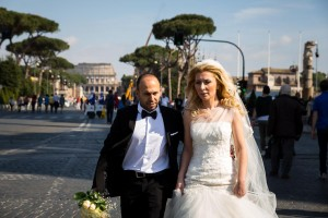 Photo reportage style photography as newlyweds walk on via dei Fori Imperiali with the Colosseum in the background.