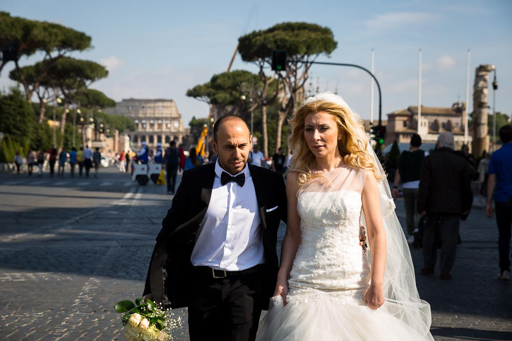 Photo reportage style photography as newlyweds walk on via dei Fori Imperiali with the Colosseum in the background. Post wedding photography.