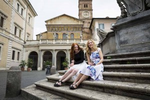Girls sitting down on the steps of Santa Maria in Trastevere in Rome Italy