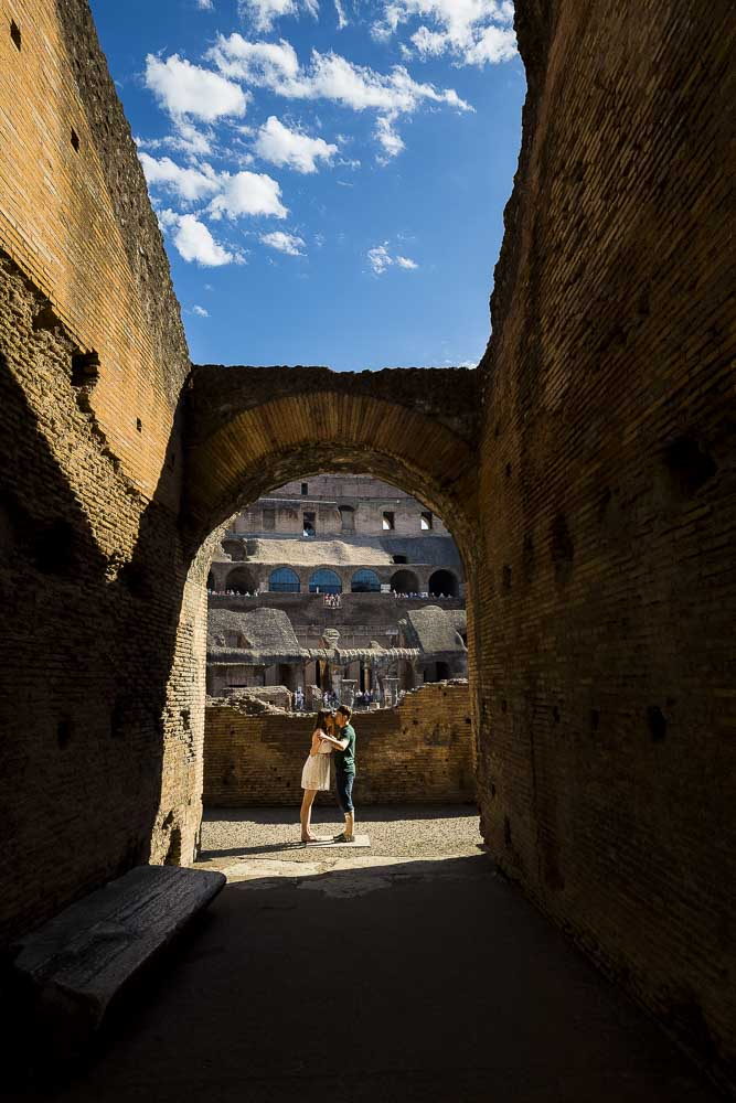 Picture taken from afar of a coupe underneath an ancient roman arch