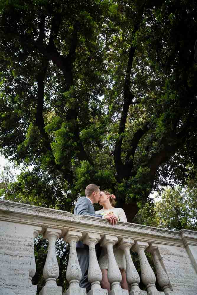 Newlywed couple kissing underneath a tree in Pincio park