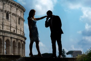 A gentleman's kiss at the Coliseum photographed during an engagement session in Rome Italy