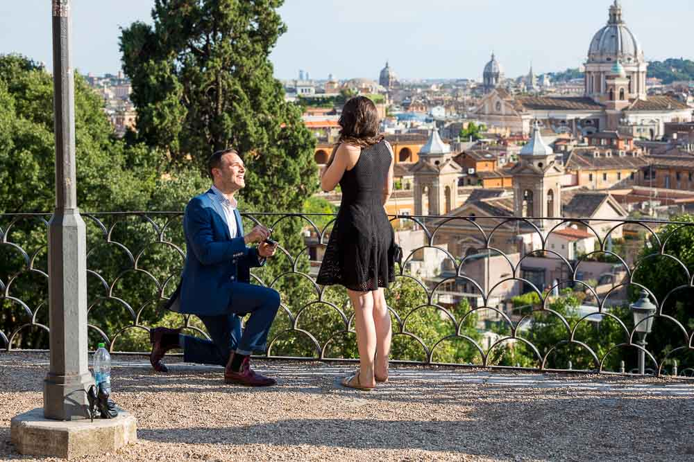 Man proposing to his girlfriend in Rome at a beautiful location. romantic secret proposal.