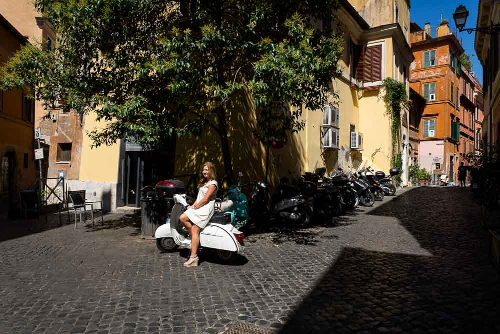 Sitting on a vespa scooter in the streets of Trastevere in Rome