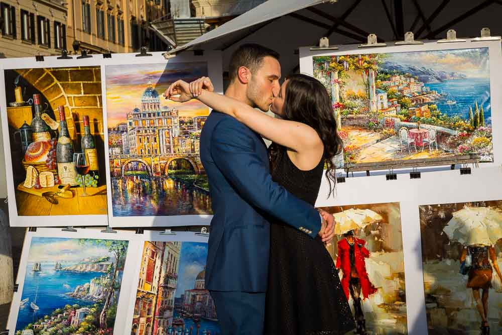 Kissing in Rome during an engagement session photographed next to artist paintings