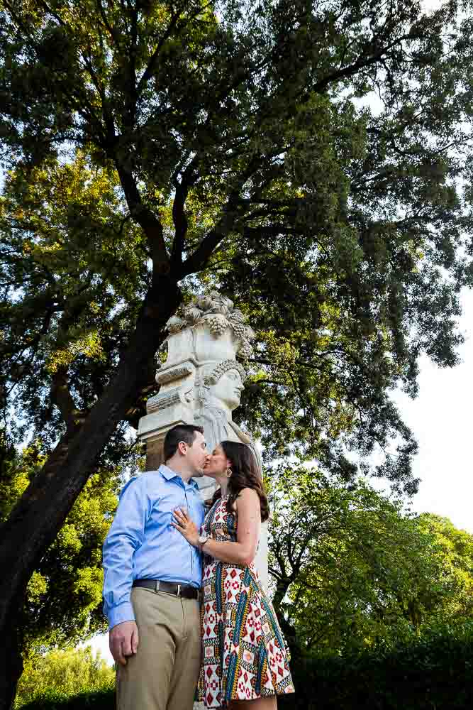 Kissing under statue and tree