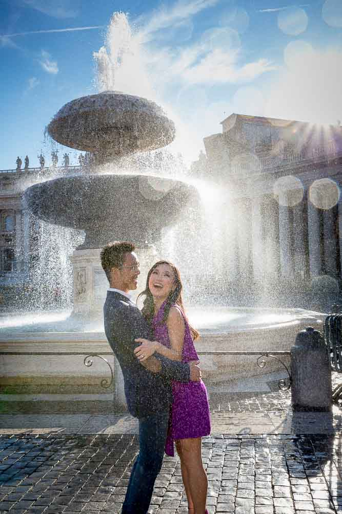 Splashing water from fountain at the Vatican square. Engagement photographer Andrea Matone Rome Italy.