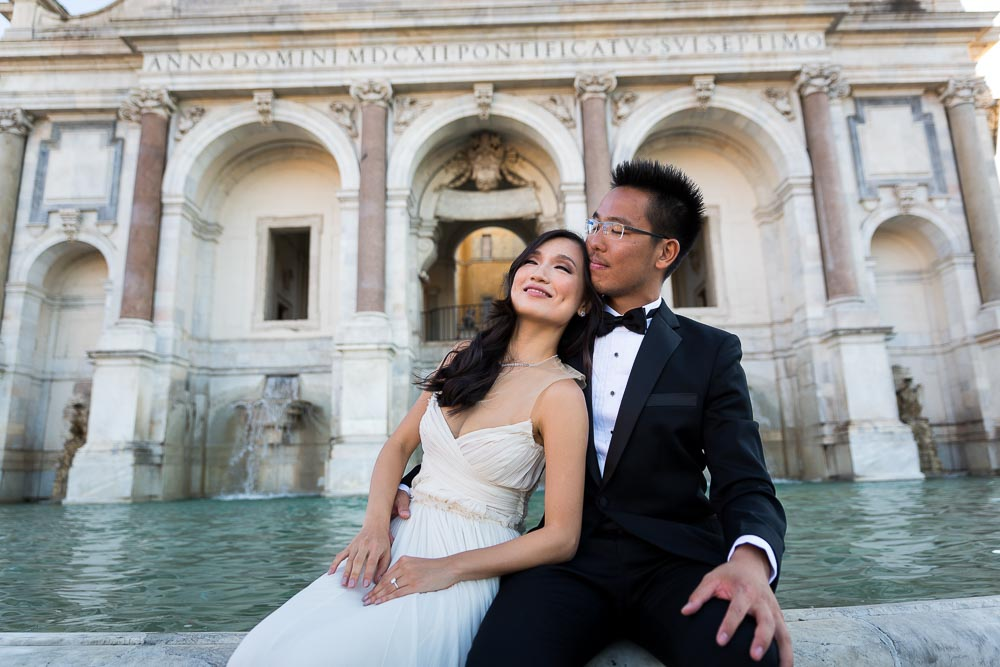 The bride rests against the groom's shoulder while sitting on the Gianicolo water fountain