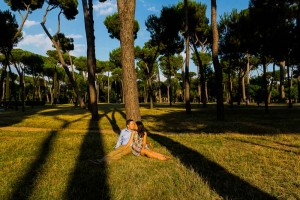 Laying down on the grass by a tree in Park Villa Borghese in Rome Italy. Image by Andrea Matone photographer