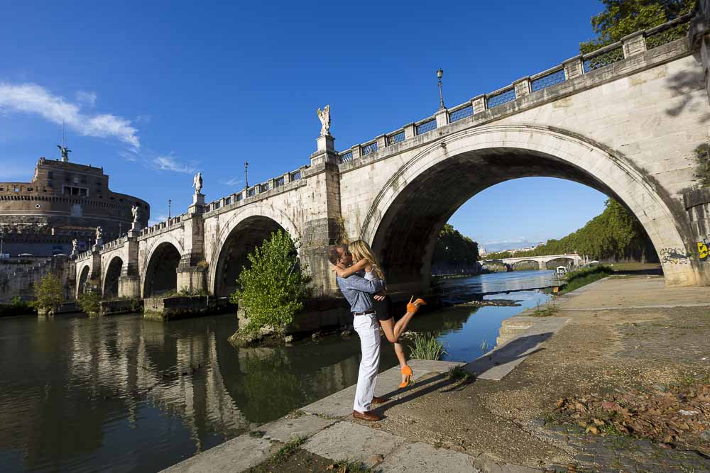 Man picking up fiancee during a photo shoot underneath the Castel Sant'Angelo bridge