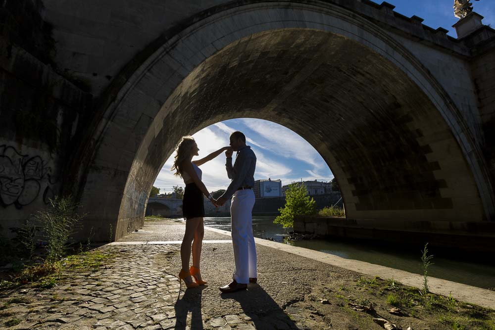Man kissing fiancee hand in silhouette under the Castel Sant'Angelo bridge