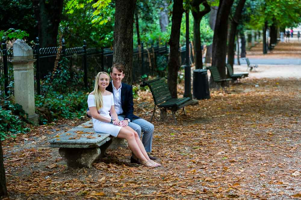 Portrait session of a couple posing and sitting down in the Villa Borghese park