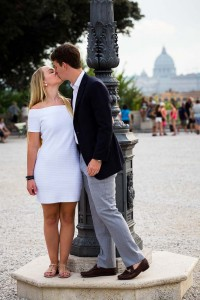 Couple romantically kissing in front of Saint Peter's dome in the distance