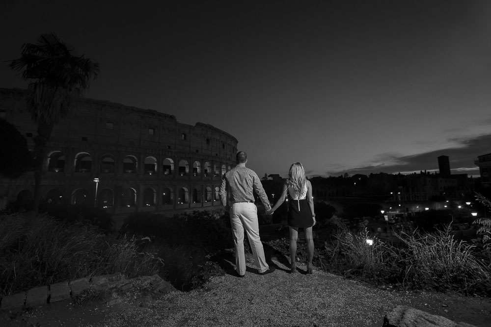 Black and white photo of an engaged couple looking at the Colosseum