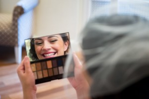 Woman with veil looking through the makeup mirror