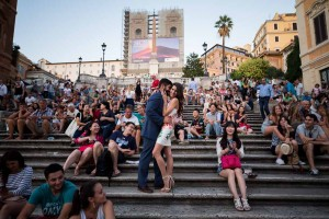 Couple posing in love among a large crowd of tourists sitting down on the stairs of Piazza di Spagna in Rome Italy