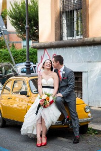 Groom and bride leaning on a yellow fiat 500 parked