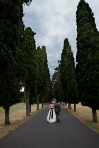 Bride and groom walking together under cypress trees in Italy