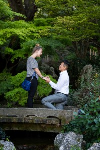 Knee down wedding marriage proposition in a park garden