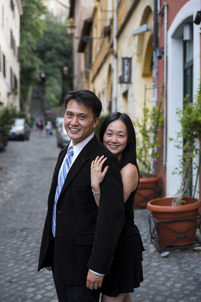 Portrait shot of a man and a woman during their engagement in Trastevere Rome. Alleyway streets setting.