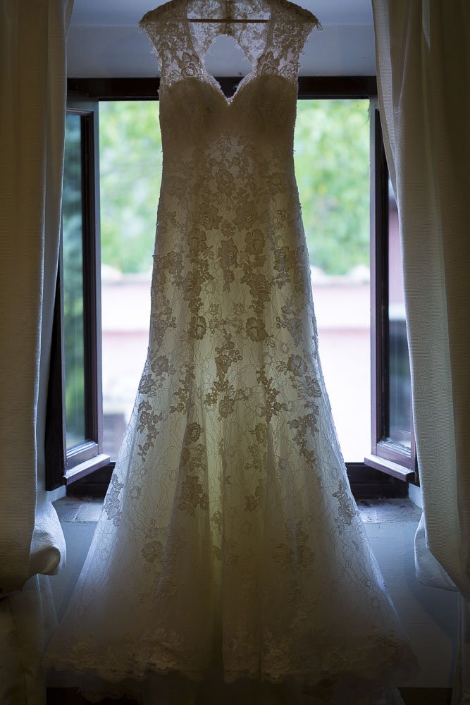 The wedding dress hanging from the window