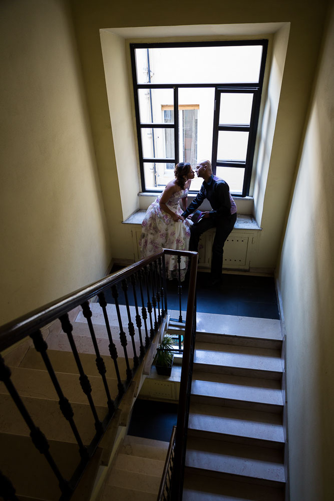 Picture of a couple sitting down on a staircase romantically kissing