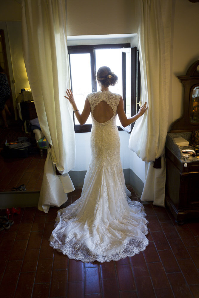 Looking out of the window wearing the wedding dress
