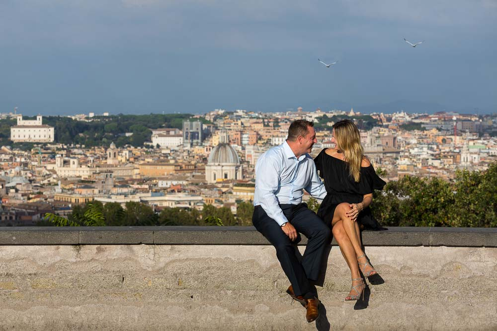 Sitting down on a wall in front of the sweeping view over the roman rooftops in Rome Italy.