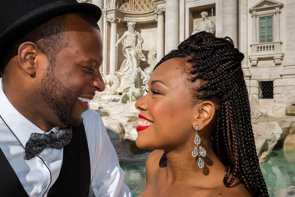 Closeup image of a couple together at the Trevi water fountain