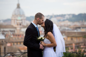 Newlywed couple kissing in front of the city of Rome