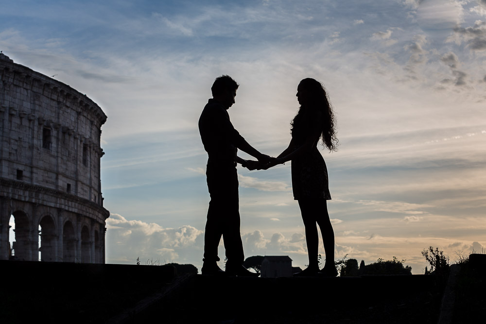 Silhouette image of a engaged couple standing before the Roman Colosseum in Rome