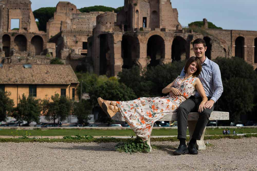 Portrait image of a couple sitting down with the Palatine hill in the background. Rome Engagement couple.