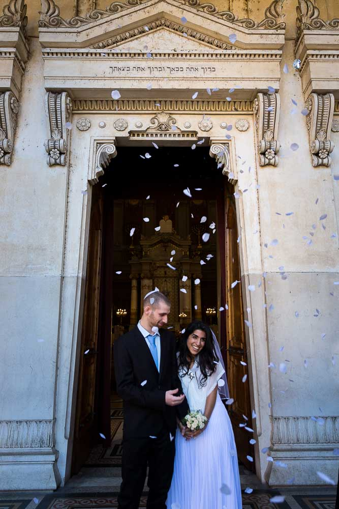Walking outside the synagogue after getting married with petals