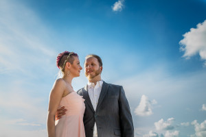Portrait picture of a couple in wedding attire surrounded by blue sky