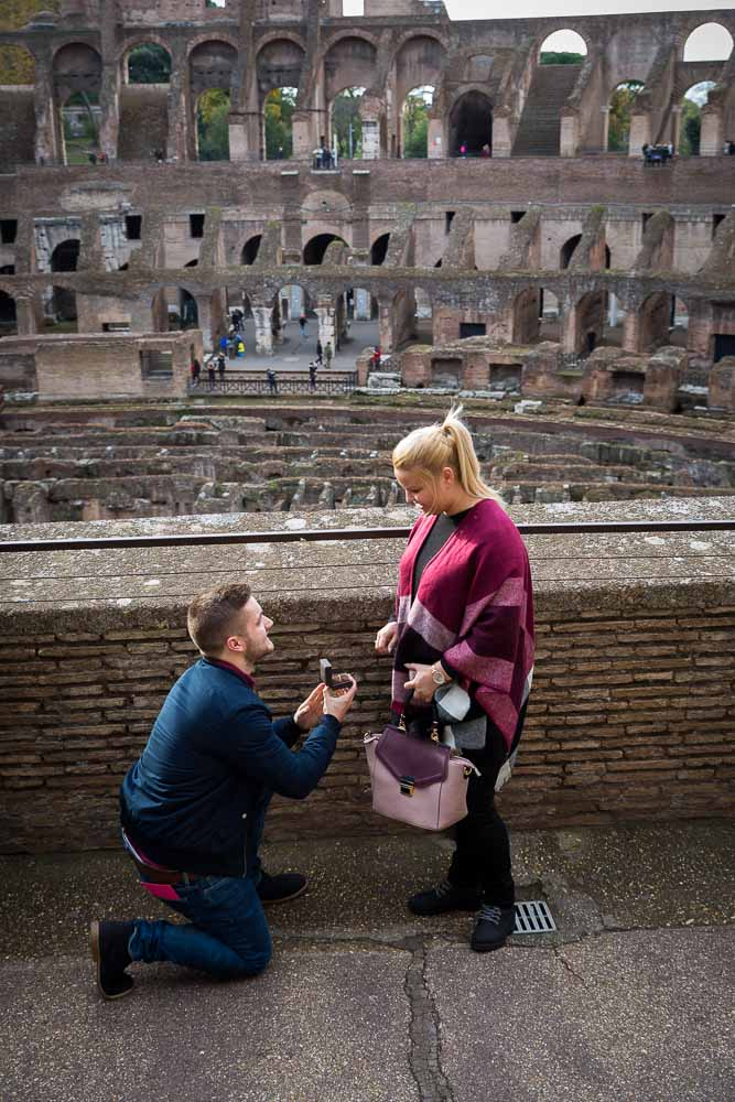 Man proposing inside the roman Colosseum in Rome Italy