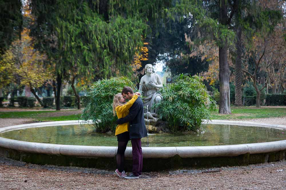 Couple photo session by a circular water fountain in parco villa Borghese