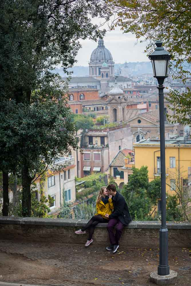 Sitting and hanging out beofre the stunning rooftop view of the city of Rome Italy during an engagement photoshoot