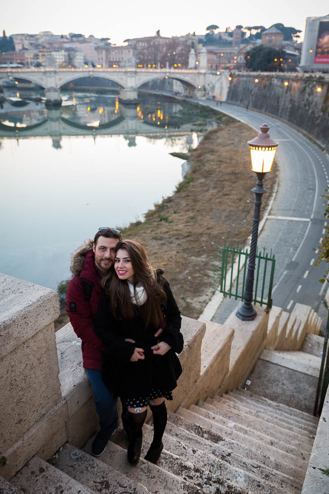 Engaged couple posing during an e-session over the Tiber river