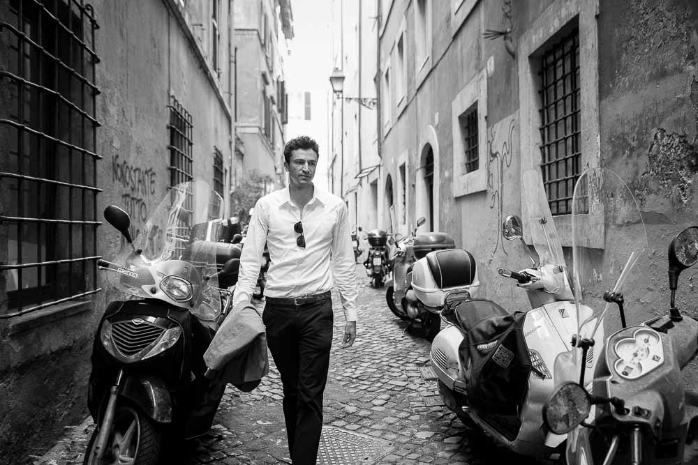 Walking in a roman alleyway among scooters and black and white photography