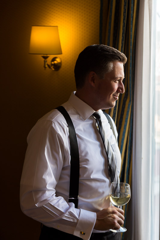 Man groom to be looking out the window