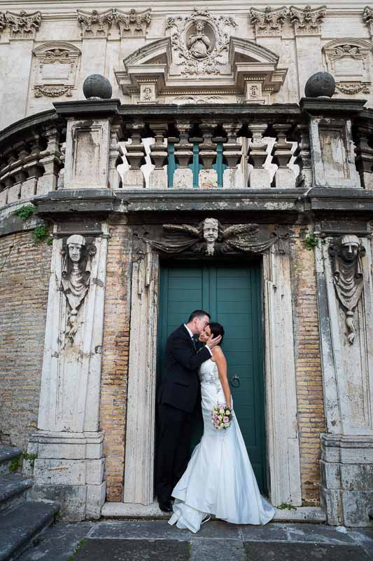 Kissing by an ancient door by a roman staircase