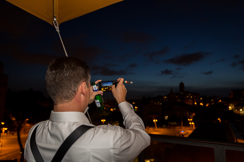 Man taking a picture of the ancient city at night