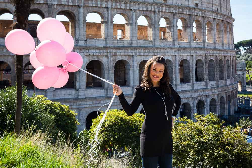 Woman holding up prenatal balloons at the Roman Colosseum during a photo session