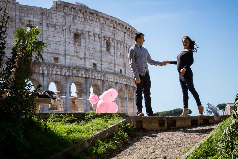 Holding hands overlooking the Colosseo. Maternity Photographer in Rome