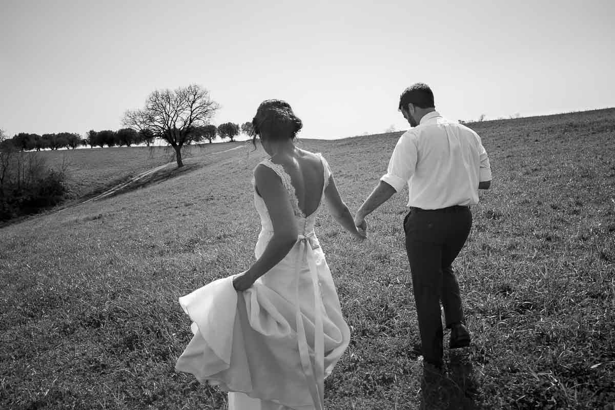Bride and groom walking together in an Italian field