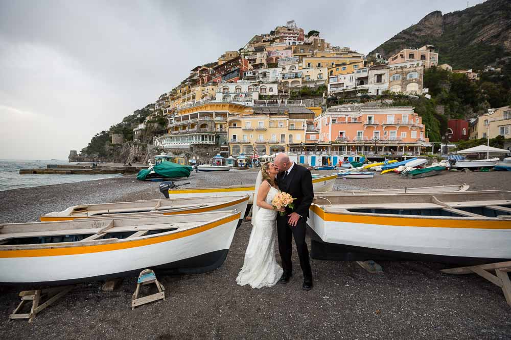 Bride and groom portrait on the beach in front of the town. Wedding photographer Positano Italy