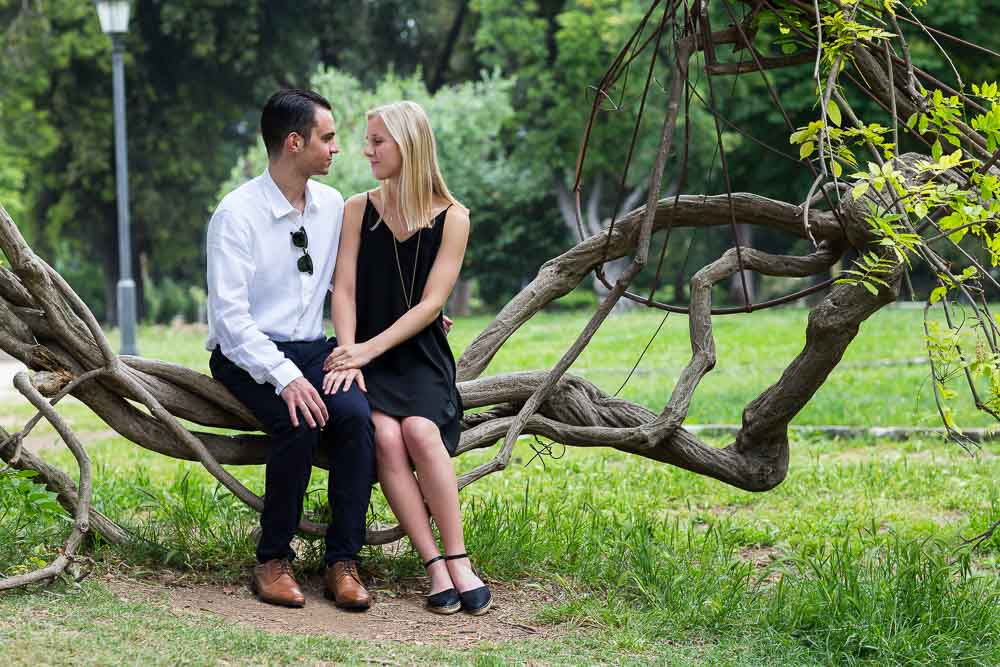 Portrait picture taken of a couple sitting down on an interesting plant seat