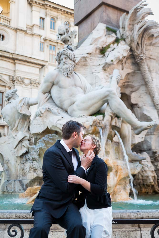 Couple kissing at Fontana dei Quattro Fiumi found in the center of Piazza Navona