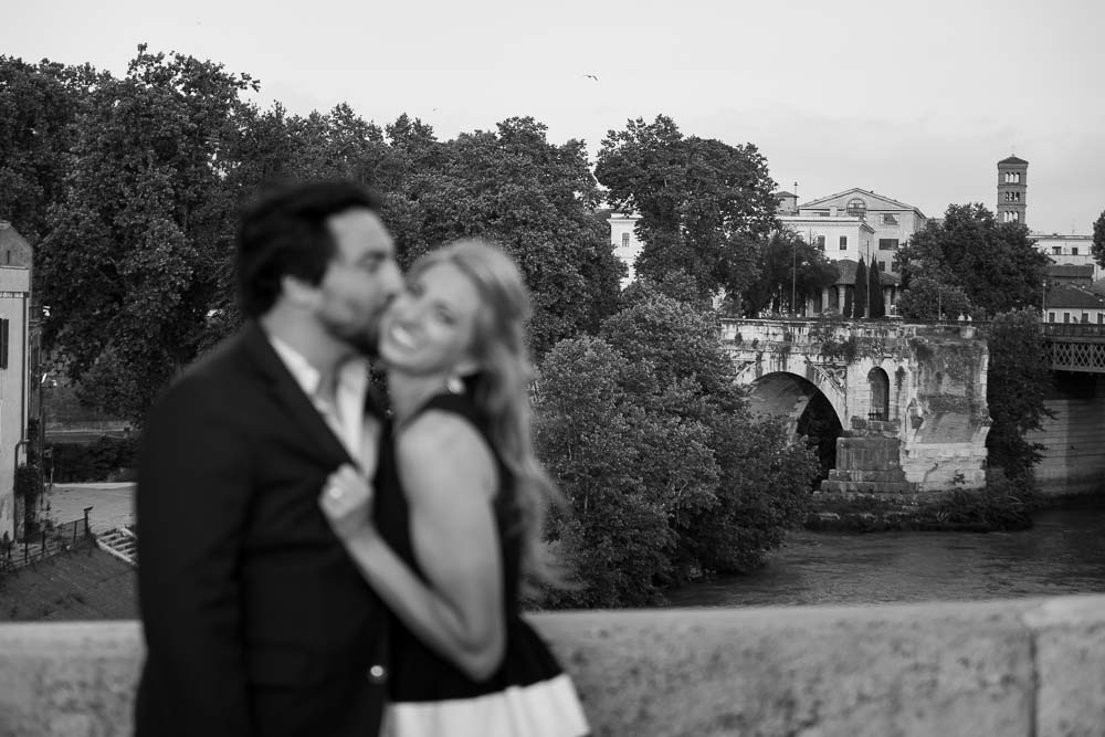 In love in Rome with an ancient distant bridge in the background