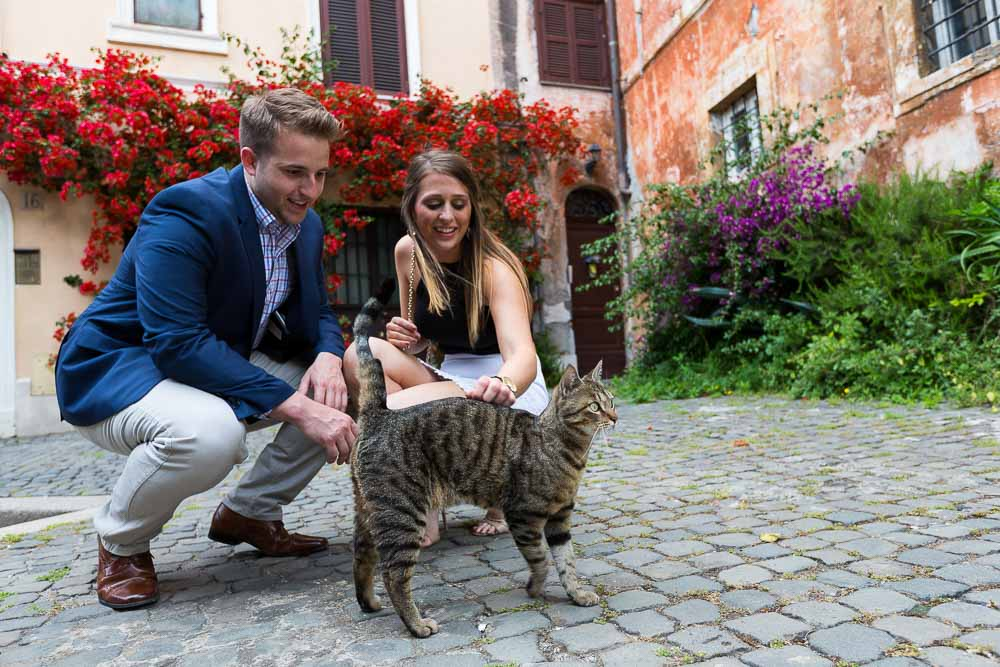 Petting the cat in a typical roman street alleyway and square